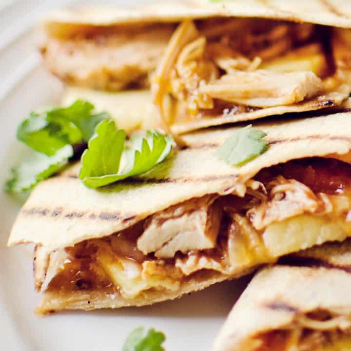 Crock Pot BBQ Chicken Pineapple Quesadillas on white plate garnished with cilantro