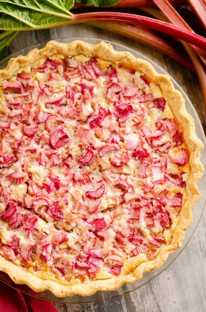 Rhubarb Custard Pie on table with stalks of rhubarb