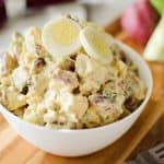 Roasted Garlic & Red Skin Potato Salad is a delicious twist on creamy potato salad with roasted garlic and bacon. This hearty salad is sure to be a hit at your next picnic or potluck!