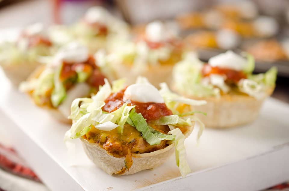 Light Mini Turkey Taco Cups - Krafted Koch - Tortilla cups filled with taco seasoned turkey and topped with lettuce, salsa and sour cream for the perfect healthy appetizer recipe! #Healthy #Appetizer #Light #Lunch