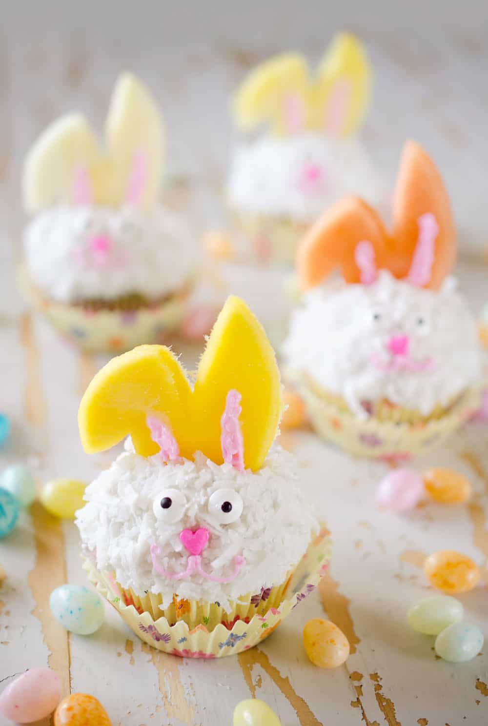 Light Coconut Cream Easter Bunny Cupcakes are a fun and healthy spring dessert recipe. Lightened up cupcakes are topped with bunny ears made from fruit, for a holiday treat kids and adults will LOVE! #Easter #Cupcakes #Light #Healthy