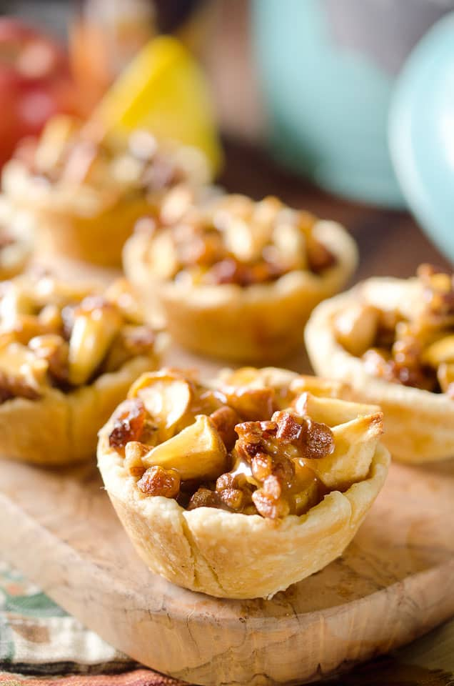 Caramel Apple Mini Pie Cups are a sweet little bite of apple pie loaded with pecans, raisins and drizzled with caramel for the perfect party appetizer or snack!