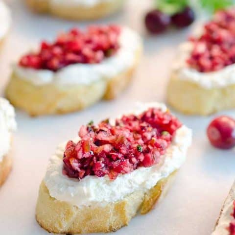Cranberry Cream Cheese Bruschetta are a fresh twist on a classic appetizer. Toasted french bread is topped with cream cheese and a spicy cranberry salsa for an hors d'oeuvre perfect for any holiday party!