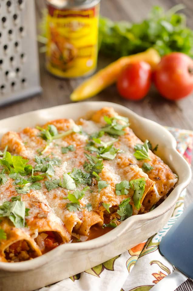 30 Minute Light Chicken Enchiladas are full of crumbled chicken & vegetables and a spicy enchilada sauce for an easy weeknight dinner!