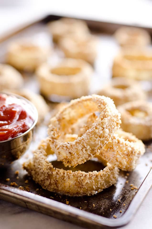 Baked Southwest Onion Rings are a lightened up version of a classic appetizer! Onions are coated in whole wheat flour, eggs, panko break crumbs and a mix of southwest spices and baked instead of fried for a healthy side dish.