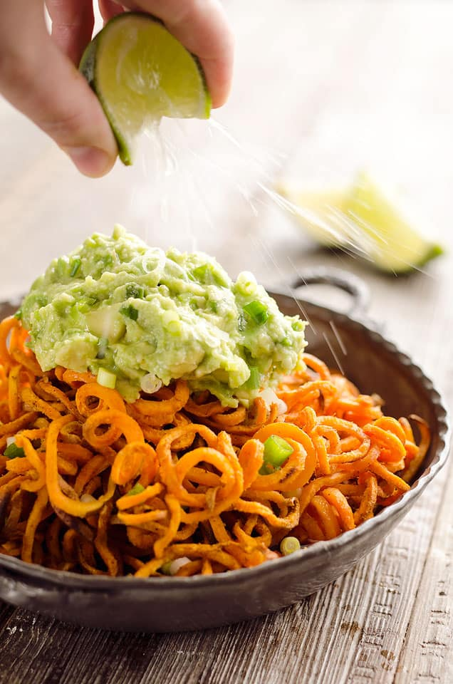 Spicy Roasted Sweet Potato Spirals with Guacamole is an amazingly delicious meatless dinner or appetizer with crispy sweet potatoes coated in garlic & chili powder and topped with a zesty guacamole.