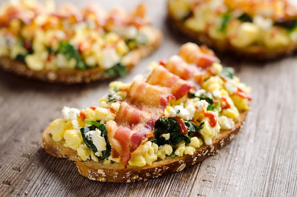 Sriracha Bacon Bleu Cheese Breakfast Toasts are a light meal bursting with bold and spicy flavors. Fluffy scrambled eggs and spinach are piled on whole wheat toast and topped with a slice of bacon, bleu cheese crumbles and sriracha for a breakfast you won't soon forget!