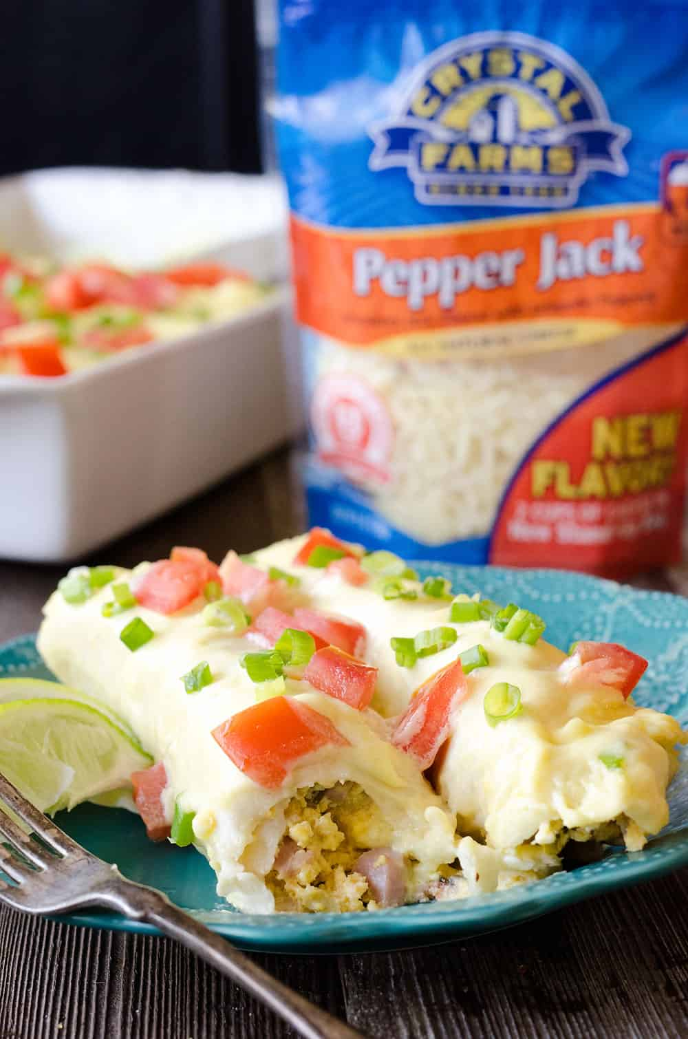 Cheesy Eggs Benedict Breakfast Enchiladas are a fun twist on brunch that will satisfy a crowd! Fluffy scrambled eggs, green chilis and leftover ham are rolled up in flour tortillas and covered with a cheesy hollandaise sauce, then topped with fresh tomatoes and green onions, for a zesty and decadent breakfast you will love!
