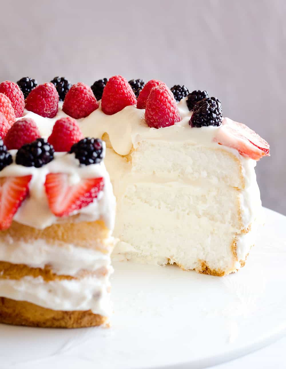 Light Berry Angel Food Cake is an easy and delicious 15 minute dessert. Angel food cake is layered with luscious white chocolate Cool Whip and topped with fresh berries for a guilt-free treat!