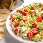 Skinny Taco Dip is a light and zesty appetizer that is a serious crowd-pleaser! This easy snack is lightened up with Greek yogurt, salsa and light cream cheese and topped with healthy avocado, tomatoes and green onions! Serve with your favorite chips for a treat everyone will love.