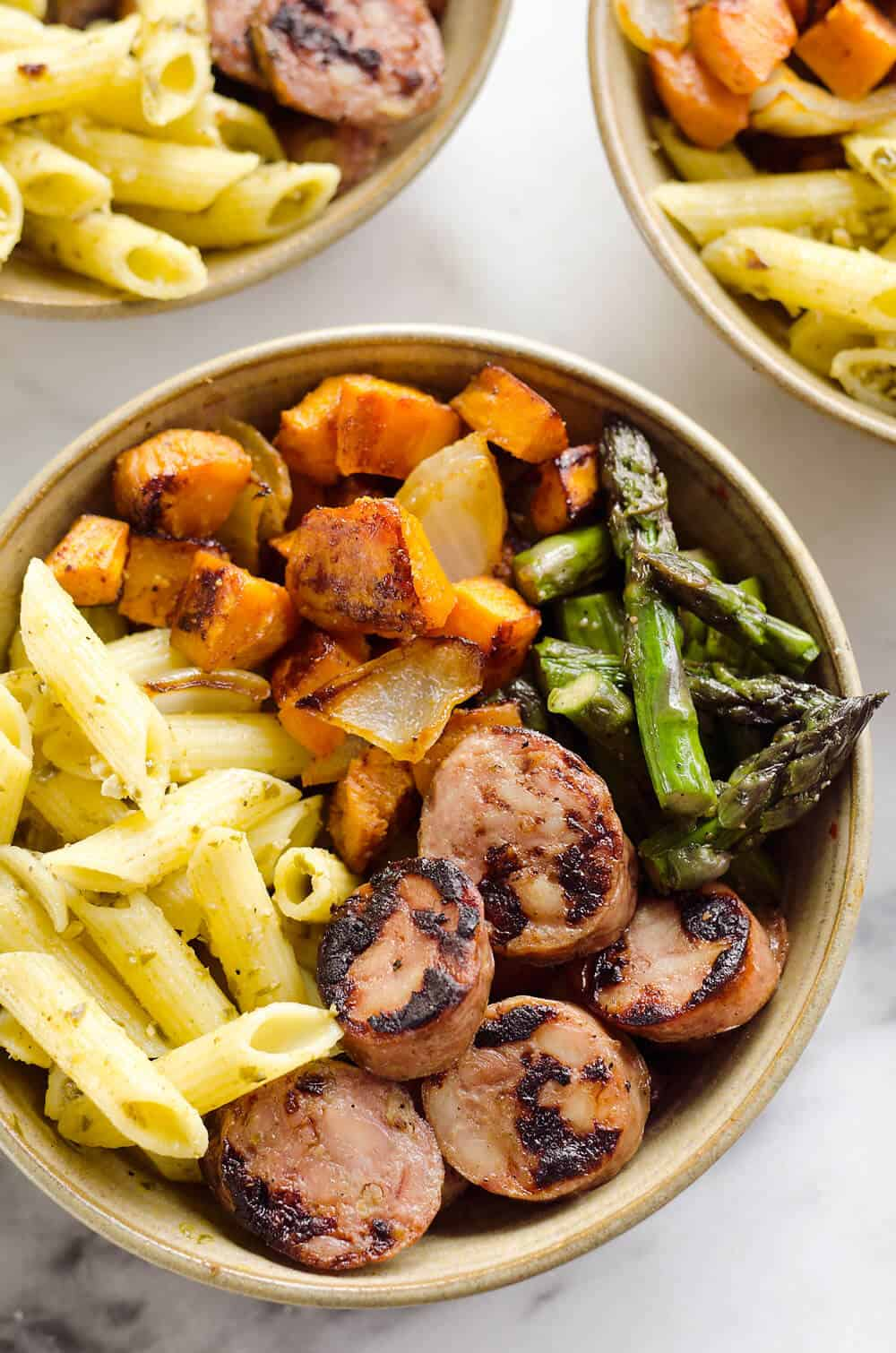 Roasted Veggie & Chicken Sausage Penne Bowls are a healthy gluten free dinner recipe bursting with bold flavors and wholesome ingredients. From chipotle roasted sweet potatoes and Aidells Chicken & Apple Sausage to Barilla Gluten Free Penne Pasta tossed in pesto, this dish is a well-rounded and satisfying meal you will love.