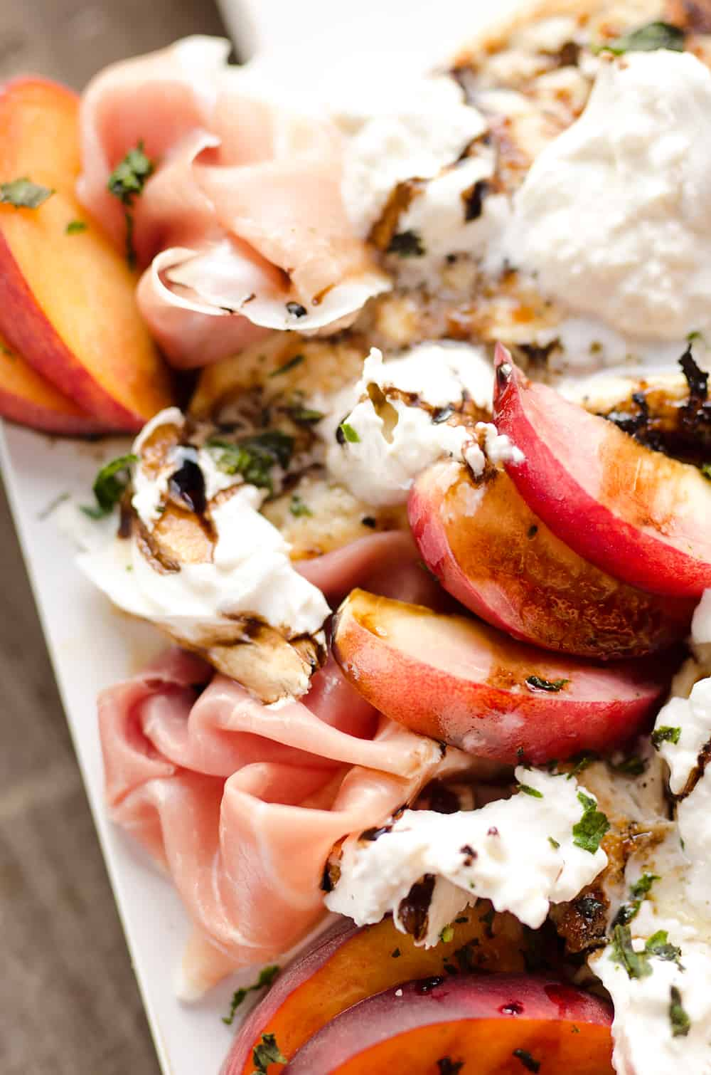 Balsamic Chicken with Peaches & Prosciutto is a deliciously simple and healthy dinner made on the grill in just 10 minutes! Grilled chicken is topped with fresh peaches and burrata cheese and finished off with a balsamic reduction and basil for a combination of flavors you will love.