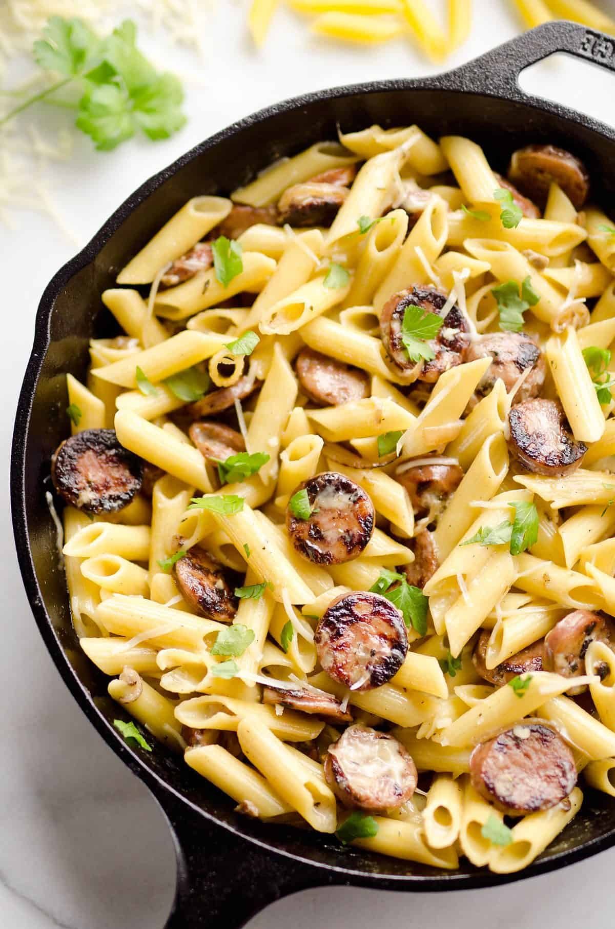 Chicken Sausage & Penne Skillet is an easy gluten free dinner idea loaded with rich flavors. Penne Pasta is tossed with a white wine and Parmesan cream sauce along with chicken apple sausage and shallots for a hearty dinner bursting with amazing flavor.