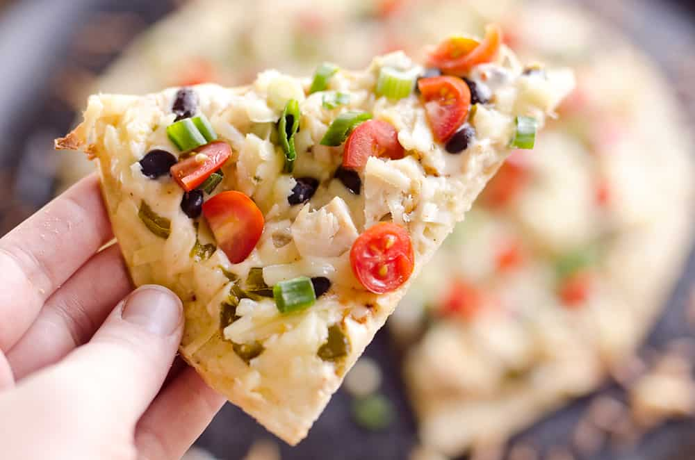 Light & Spicy Southwest Chicken Pizza is an easy recipe bursting with bold and spicy flavors. A thin and crispy crust is topped with shredded chicken, black beans and jalapeños and finished off with pepper jack cheese, fresh tomatoes and green onions for a delicious weeknight dinner idea.
