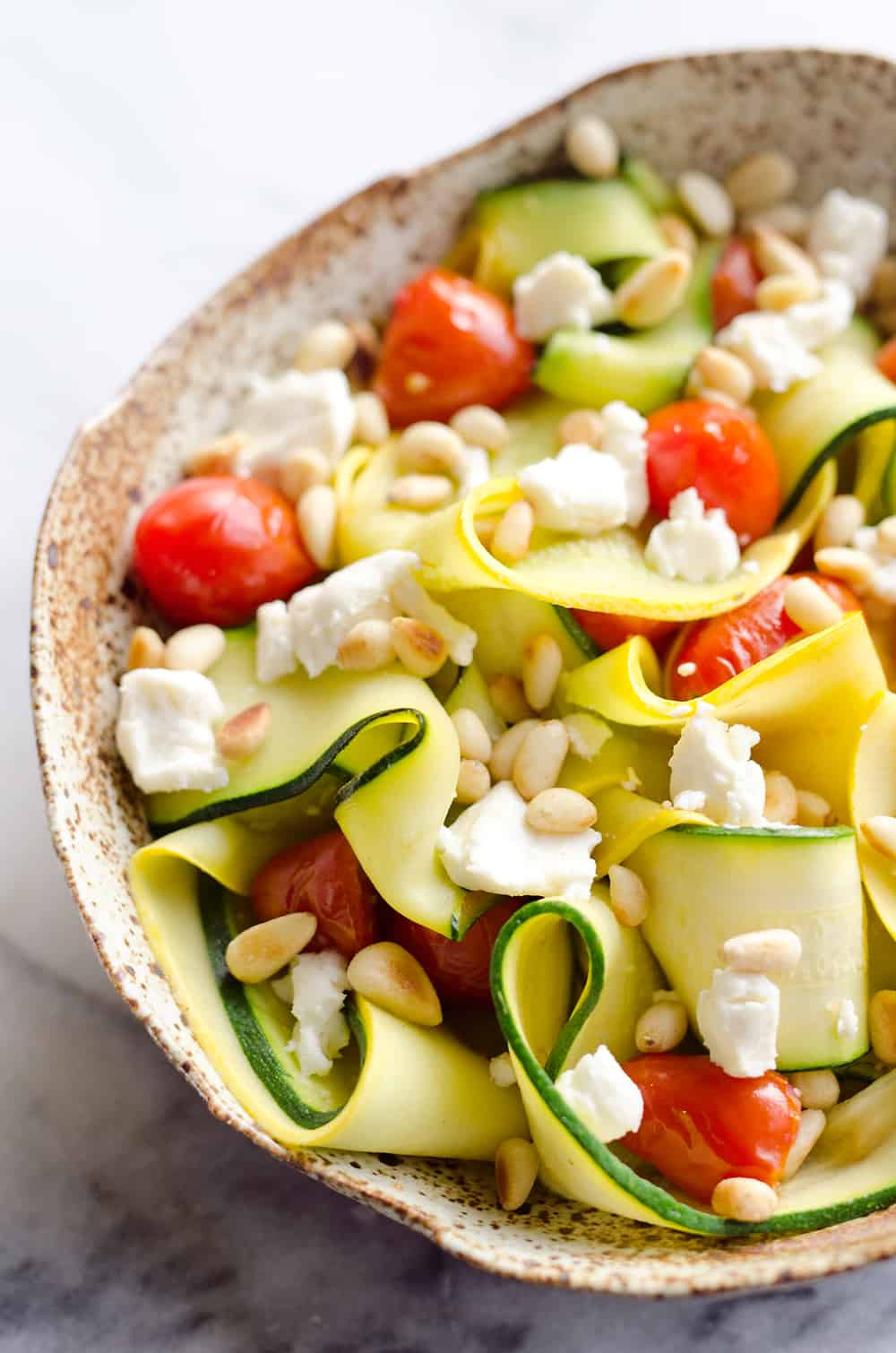 Ribboned Squash & Zucchini Salad is a fresh and healthy vegetarian salad with light veggies, toasted pine nuts, creamy goat cheese and balsamic glaze. Pair it with some grilled shrimp or chicken for an amazing and flavorful dinner you won't forget!