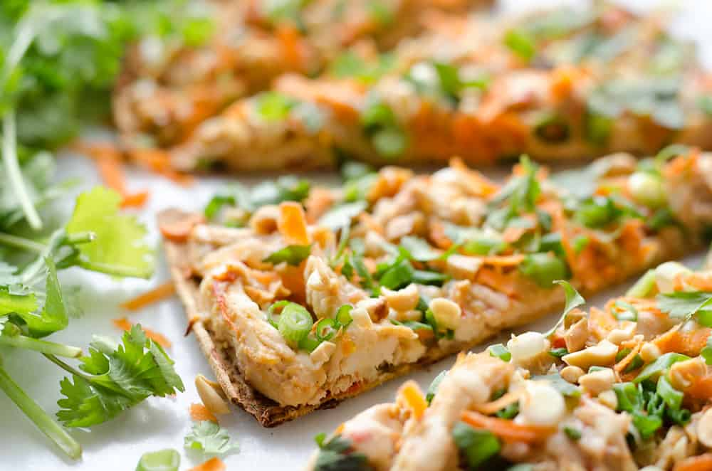 Light Thai Peanut Chicken Flatbread is a quick and healthy recipe perfect for a weeknight dinner! A thin and crispy flatbread is topped with Crock Pot Thai Peanut Chicken, cheese and crunchy vegetables and peanuts!