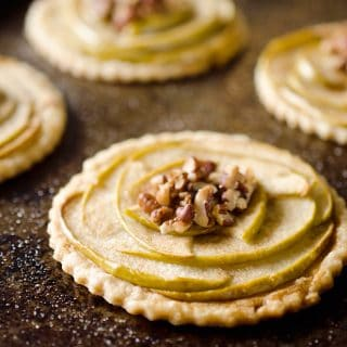 Mini Apple & Browned Butter Tarts are a perfectly light treat with great fall flavors! This dessert includes a flaky pie crust topped with apples and pecans and finished off with decadent browned butter for a bite-sized sweet perfect for holiday parties.