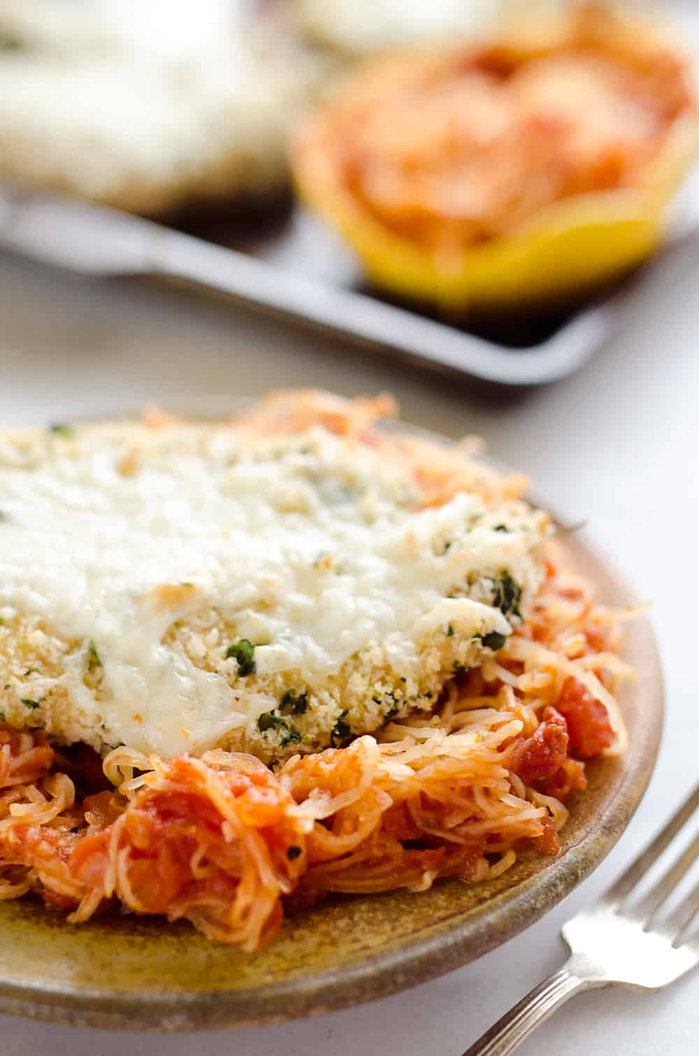 Skinny Spaghetti Squash Chicken Parmesan is a healthy twist on the traditional classic. Lightly breaded chicken breasts are baked and served with low-carb spaghetti squash and marinara sauce for a comforting dinner your family will ask for again and again!