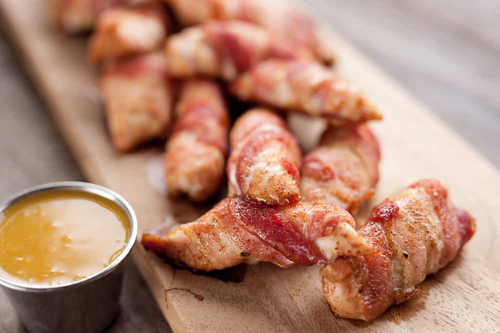 Sweet & Spicy Bacon Wrapped Turkey Tenders are a delicious appetizer paired with a homemade honey mustard for the ultimate game day finger food! They also make a great dinner idea with a side of rice and veggies.