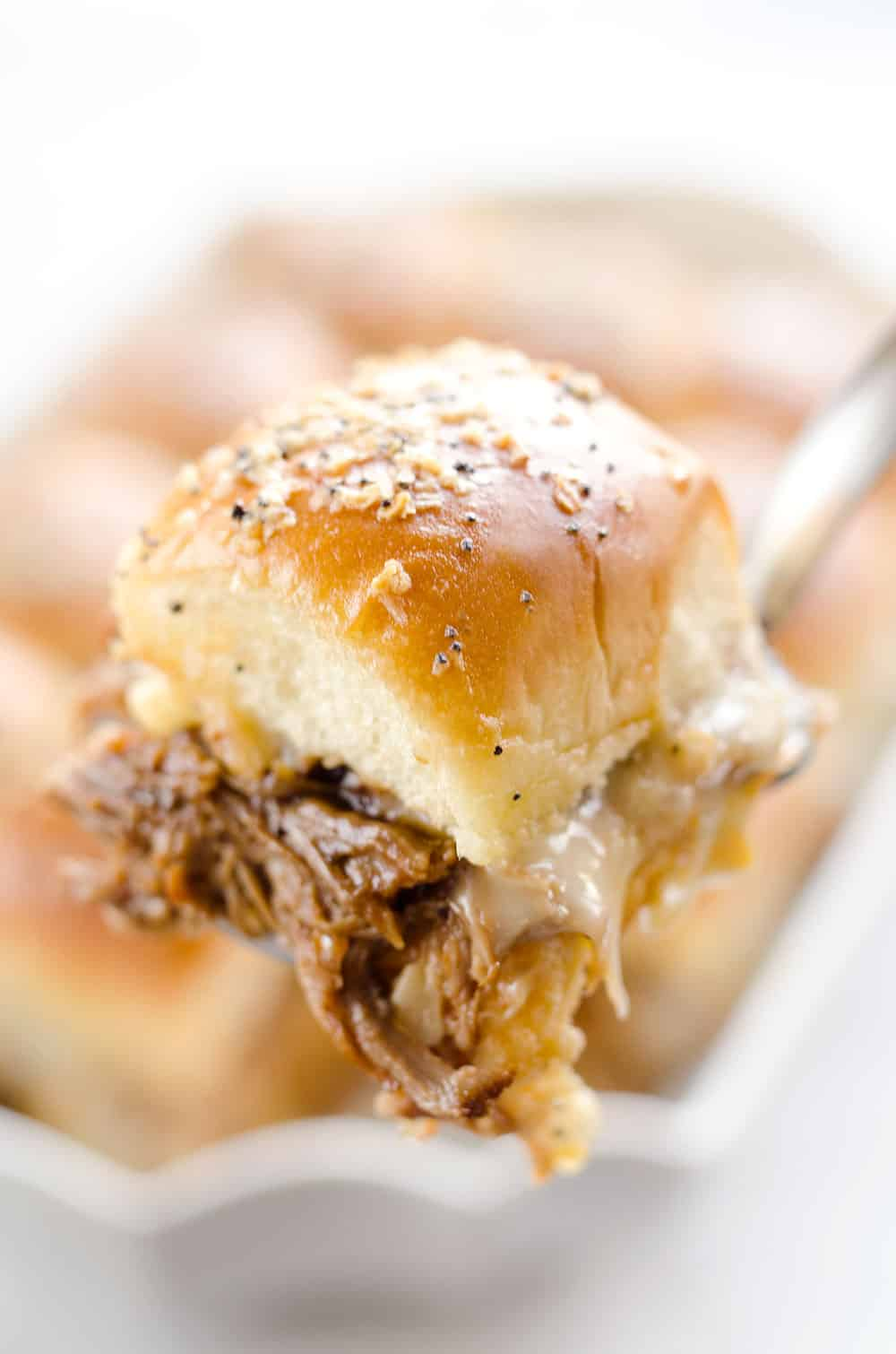 Cheesy BBQ Pork Baked Sliders are an easy family friendly meal with BBQ Pulled Pork and creamy Muenster cheese layered on Hawaiian buns with a butter sauce