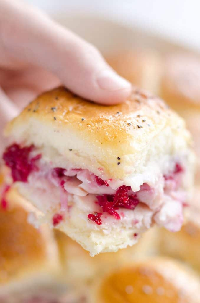 Cheesy Cranberry Turkey Baked Sliders held in hand