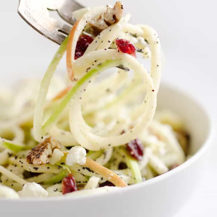 Spiralized Apple Cranberry Salad on fork with walnut