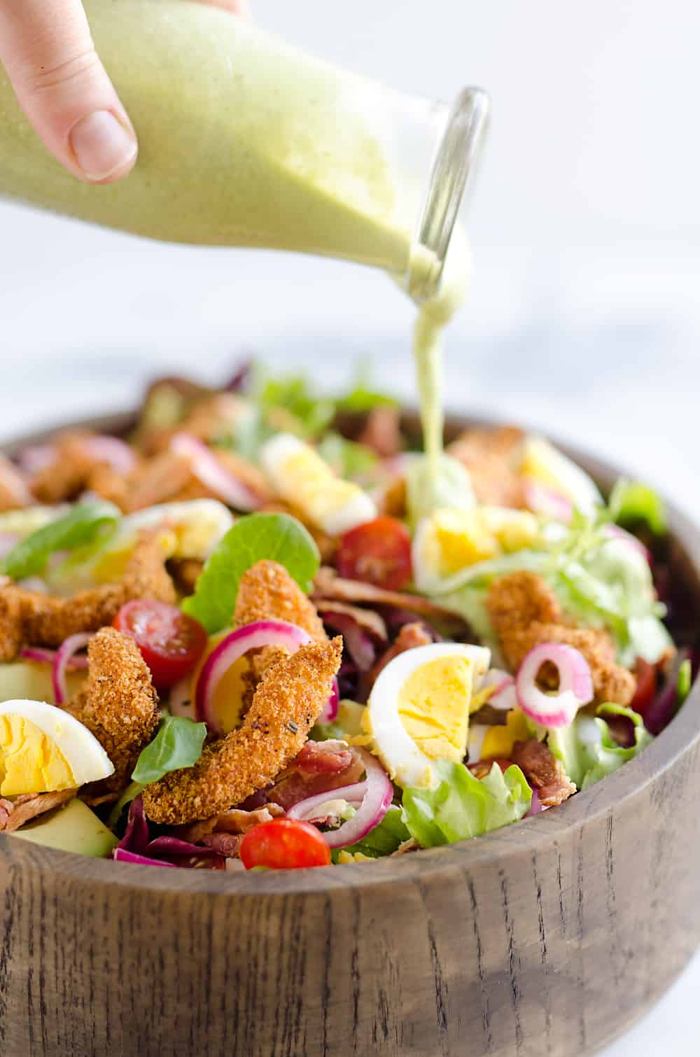 Crispy Chicken & Avocado Cobb Salad is an easy 20 minute salad recipe made in your Airfryer with Gold'n Plump Chipotle Adobo SHAKERS, bacon, veggies, lightly pickled onions and a creamy Avocado Lime Green Goddess Sauce. This hearty salad is a healthy dinner idea bursting with bold flavor and crunch!
