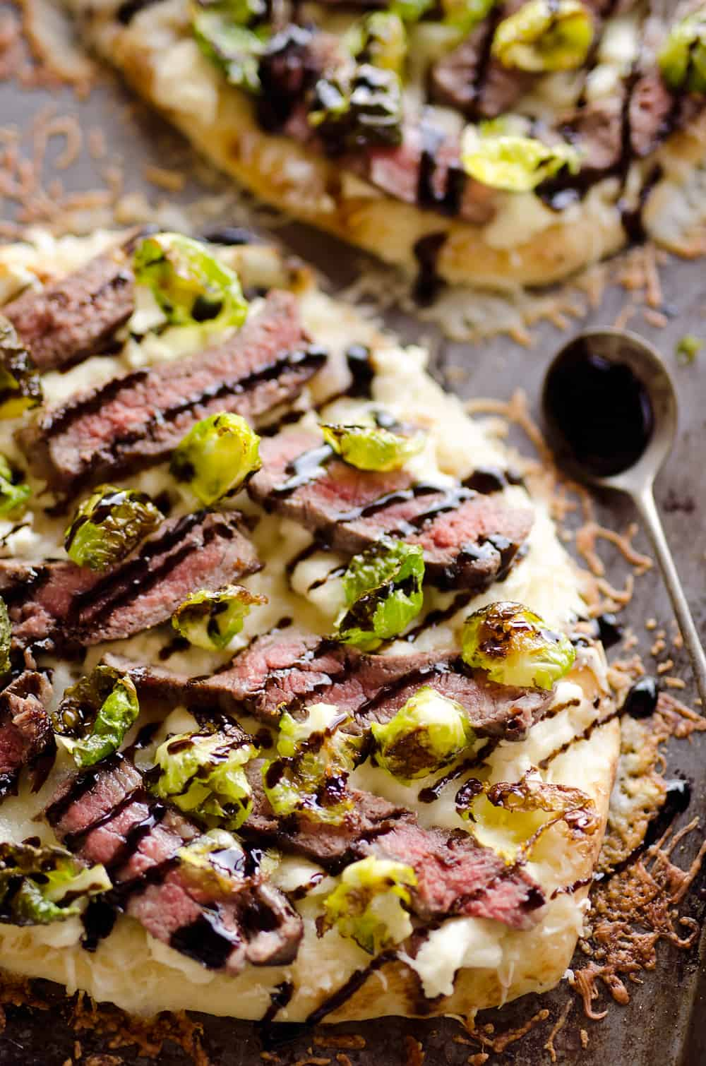 Steak, Goat Cheese & Roasted Brussels Sprout Flatbread is a hearty dinner idea bursting with bold flavors. A chewy naan bread is topped with goat cheese, grilled steak, roasted brussels sprout leaves and a balsamic glaze for a delicious and unique recipe you will make again and again!