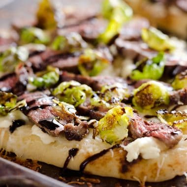 Steak, Goat Cheese & Roasted Brussels Sprouts Flatbread on sheet pan with browned cheese