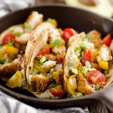 Tortilla Crusted Fish Tacos with Avocado Crema are a healthy and easy weeknight meal you can make in just 20 minutes with your Airfryer! Crispy Tortilla Crusted Tilapia is layered in a grilled corn tortilla with avocado crema and fresh tomatoes for a flavorful dinner recipe the whole family will love.