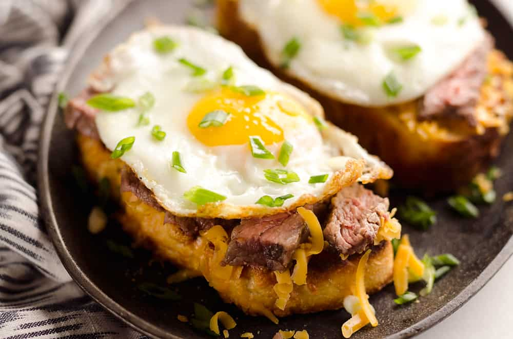 Breakfast Steak & Cheddar Toasts are a rich and decadent recipe filled with all the best parts of brunch. Tender steak is layered on top of a cheesy toast and topped with a sunny side up egg and scallions.