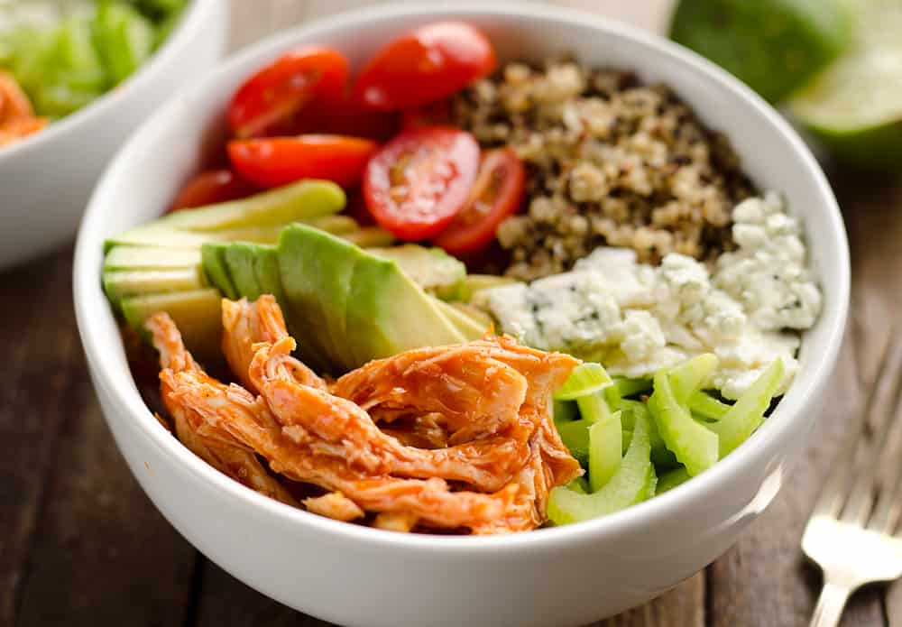 Buffalo Chicken & Quinoa Veggie Bowls are a light and healthy dinner recipe loaded with wholesome vegetables and grains, shredded chicken tossed in spicy buffalo sauce and bleu cheese crumbles for amazing flavor!