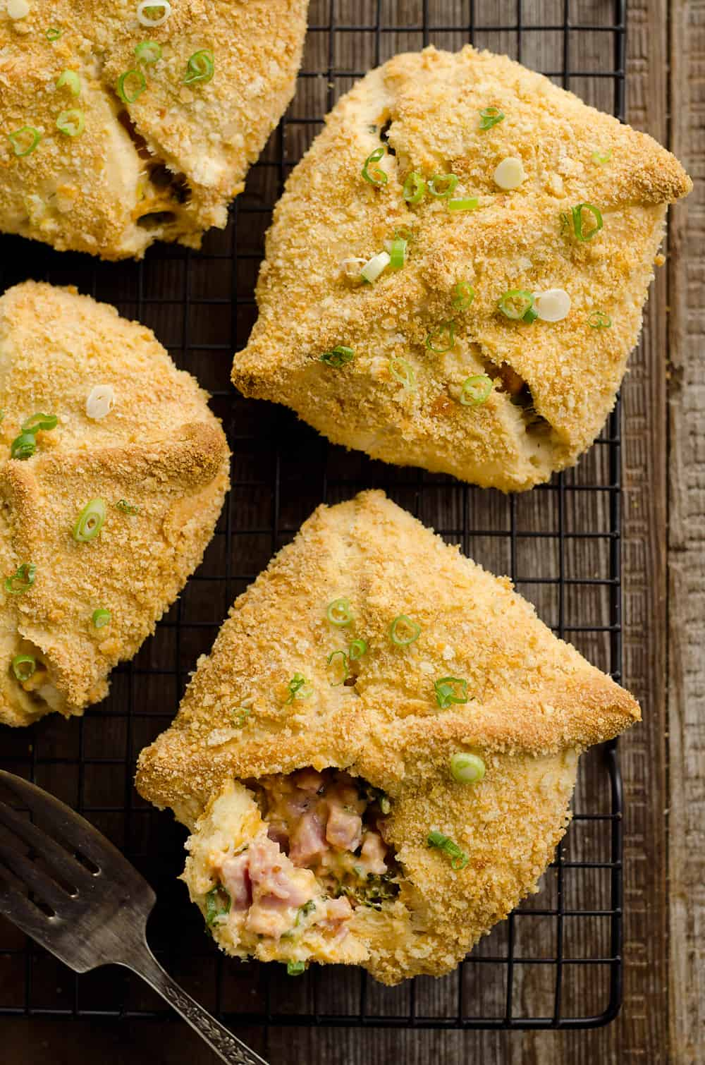 Cheesy Hot Ham & Broccoli Crescent Pockets are a family friendly dinner idea perfect for using up leftover ham! Flaky crescents are filled with a cheddar, broccoli and ham mixture and topped with buttery croutons.