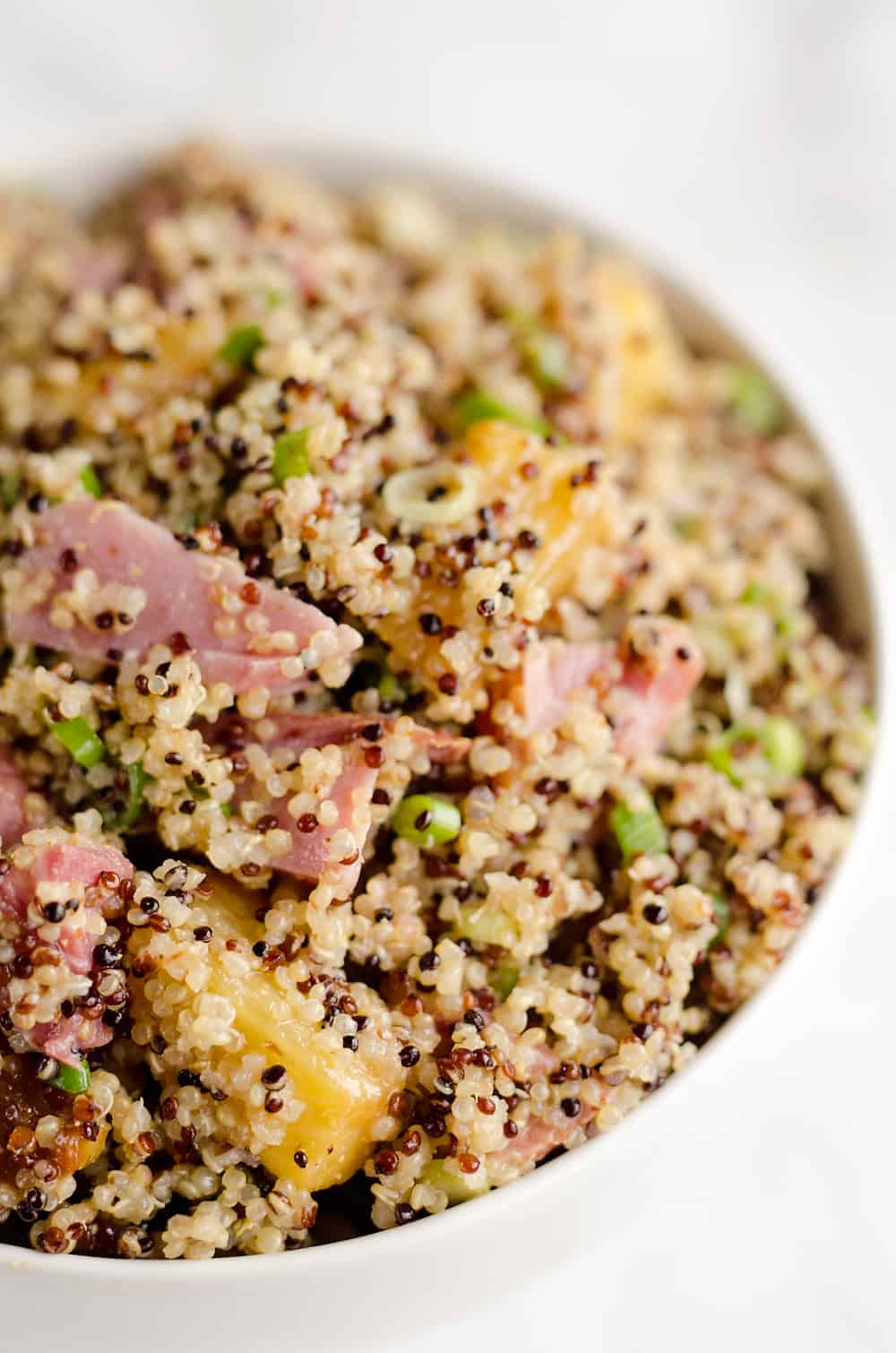 Roasted Pineapple & Ham Quinoa Salad is an easy recipe using up leftover ham with the perfect combination of sweet, salty and smokey flavors. Crunchy quinoa and oven roasted pineapple and ham are tossed with a Light Honey Dijon Vinaigrette for an easy 5 ingredient salad.