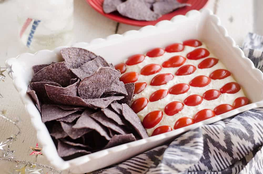 Patriotic Flag Parmesan Garlic Chip Dip is a festive appetizer recipe perfect for a holiday party with red, white and blue colors! A creamy Parmesan garlic dip is topped with cherry tomatoes and served with blue corn tortilla chips for a delicious dish sure to be a crowd pleaser.