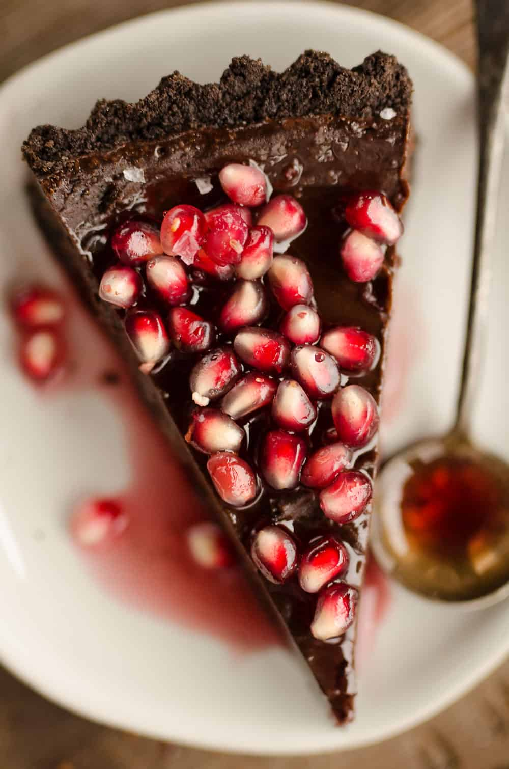 Salted Dark Chocolate Pomegranate Tart slice on plate