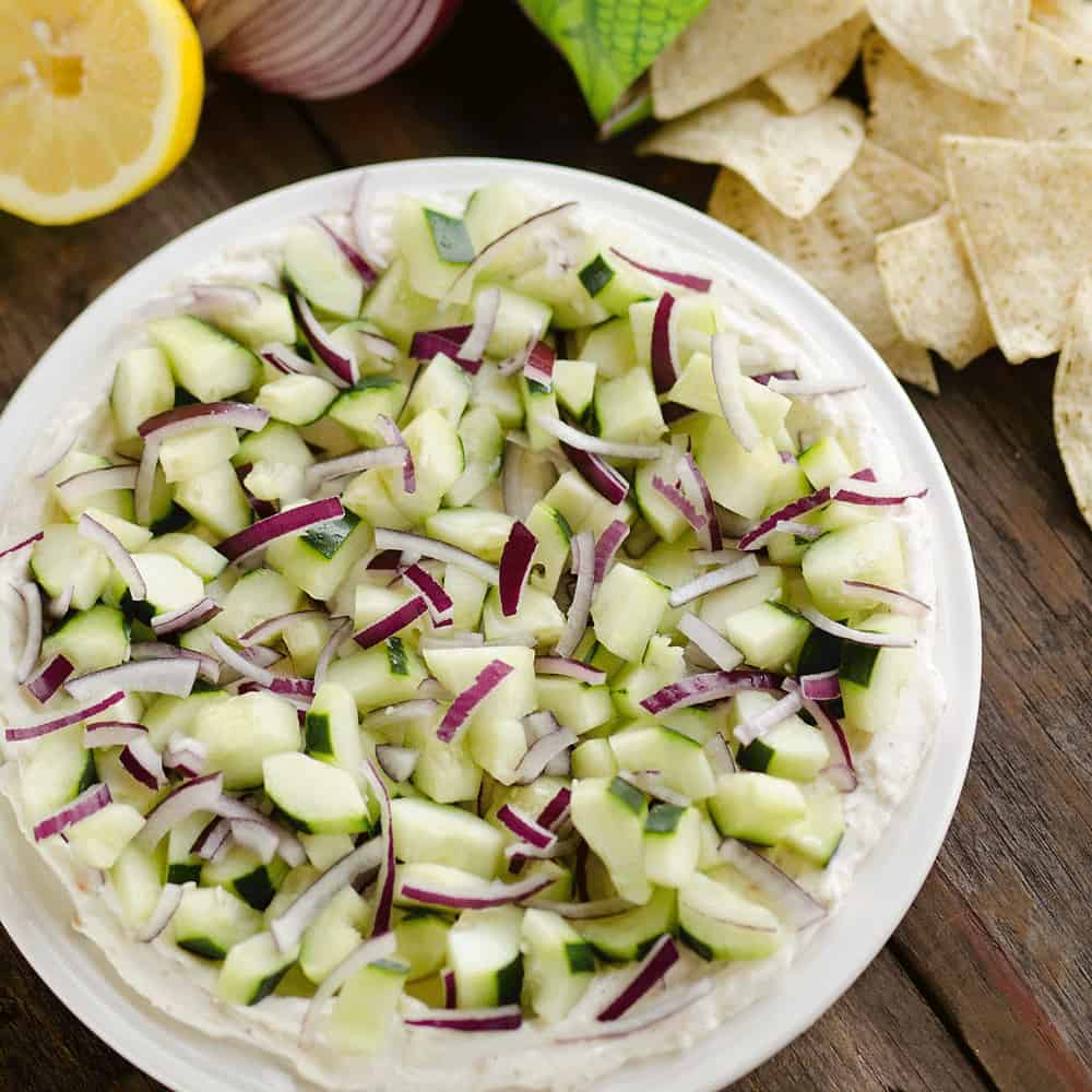 Creamy Cucumber Layered Dip is an easy 10 minute recipe perfect for a flavorful summer snack. A lightened up layer of creamy goodness is topped with fresh cucumbers and onions and served with Mission Organics Tortilla Chips for a wholesome dish you will love!