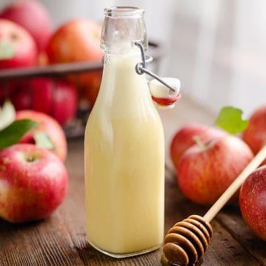 Light Apple Cider Vinaigrette bottle with apples