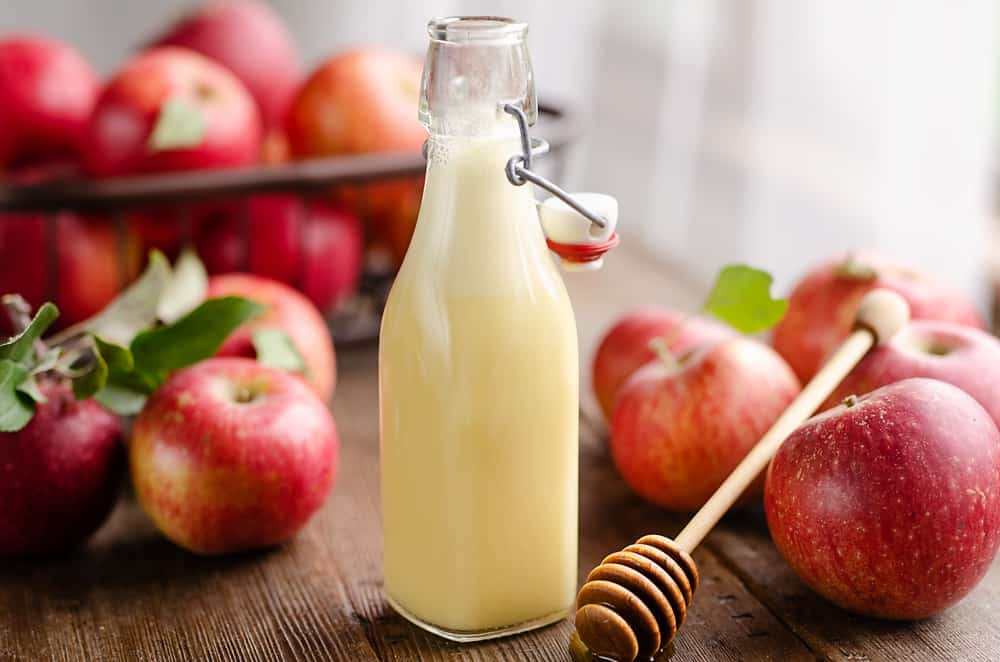 Light Apple Cider Vinaigrette bottle with apples
