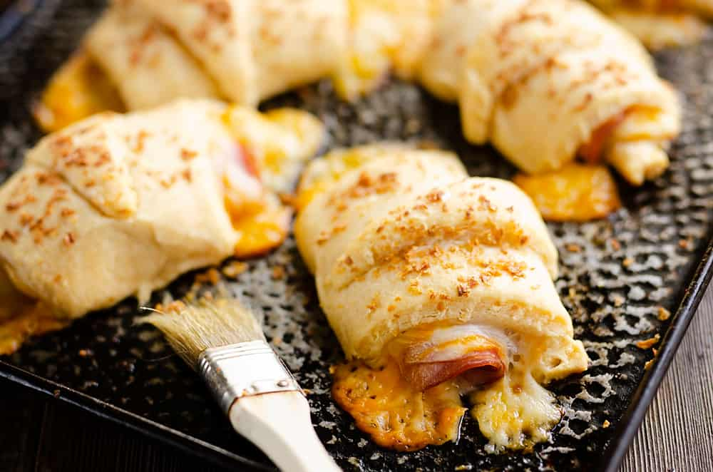 Hot Ham & Cheese Roll Ups on cookie sheet with brush