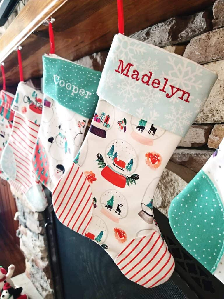 homemade personalized Christmas stockings hanging on fireplace mantel