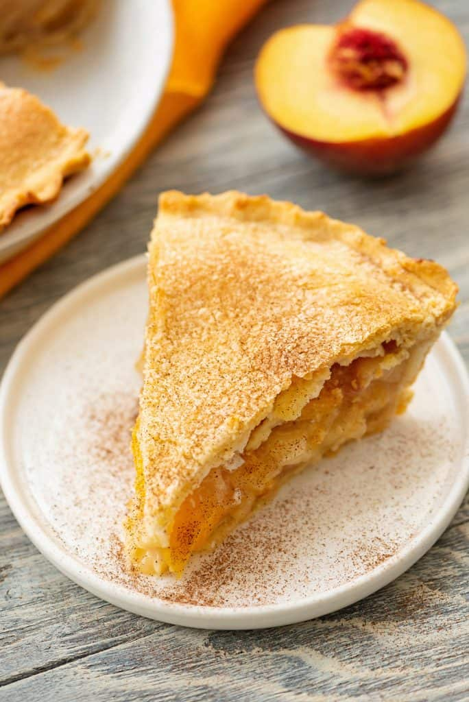 Homemade Peach Pie slice served with peach