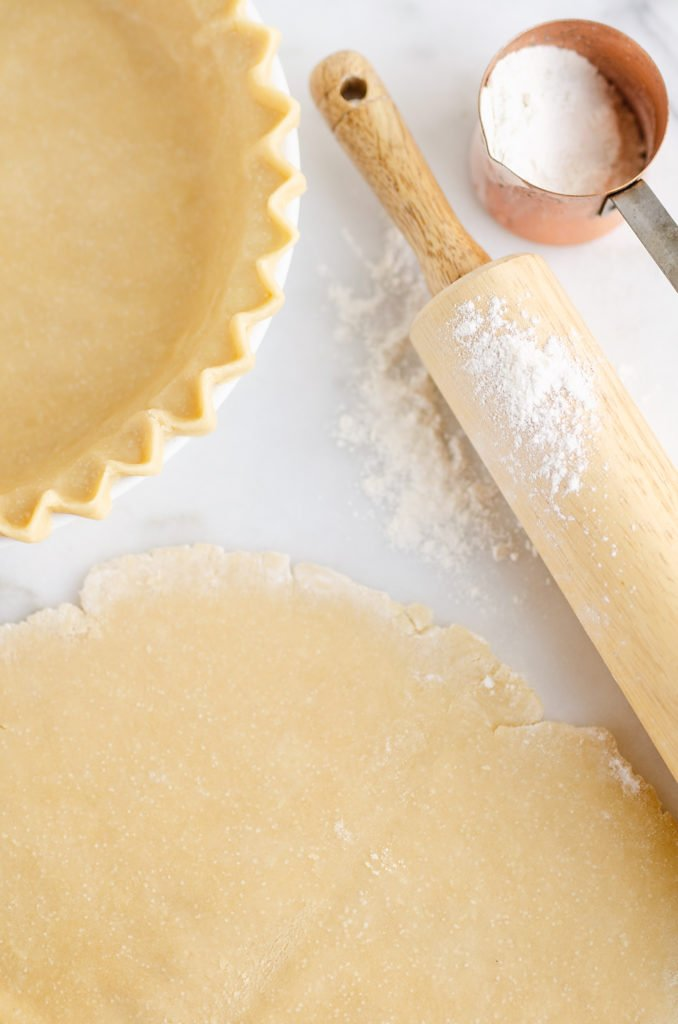 Flakey Pie Crust rolled out on marble counter with rolling pin