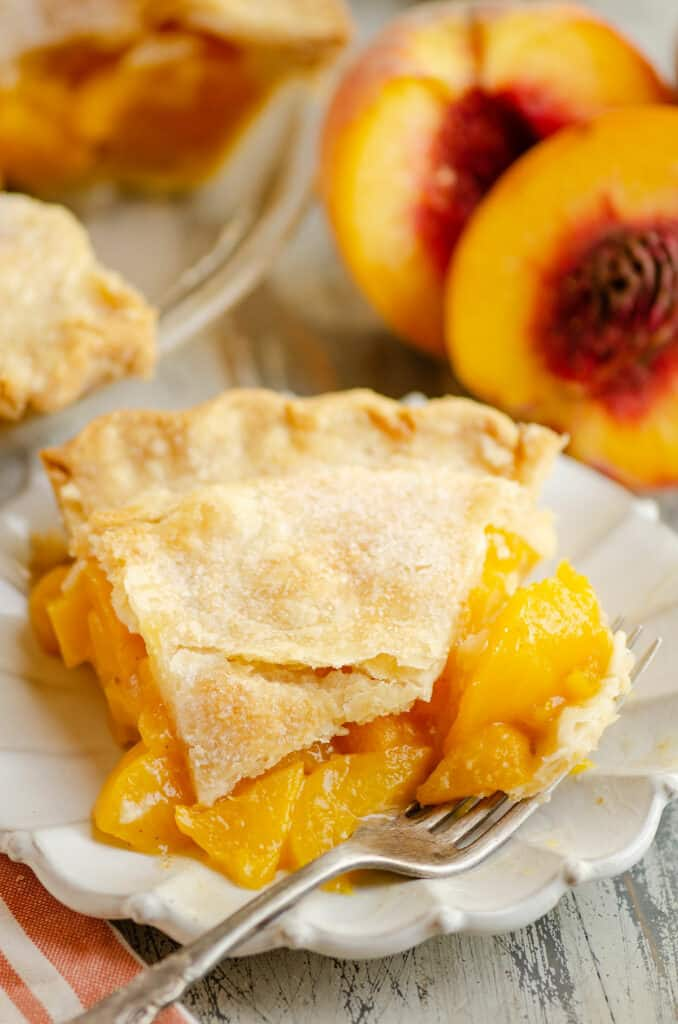slice of peach pie on plate with bite on fork