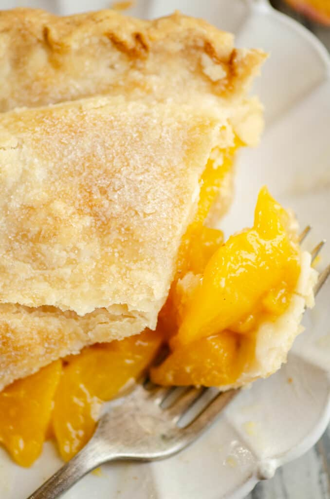 bite of peach pie on fork with slice