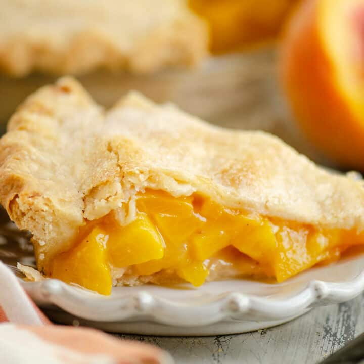 slice of peach pie on plate with peaches
