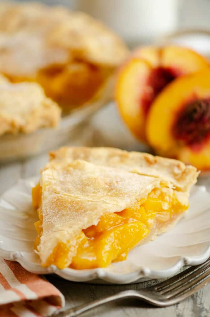 slice of peach pie on plate next to peaches