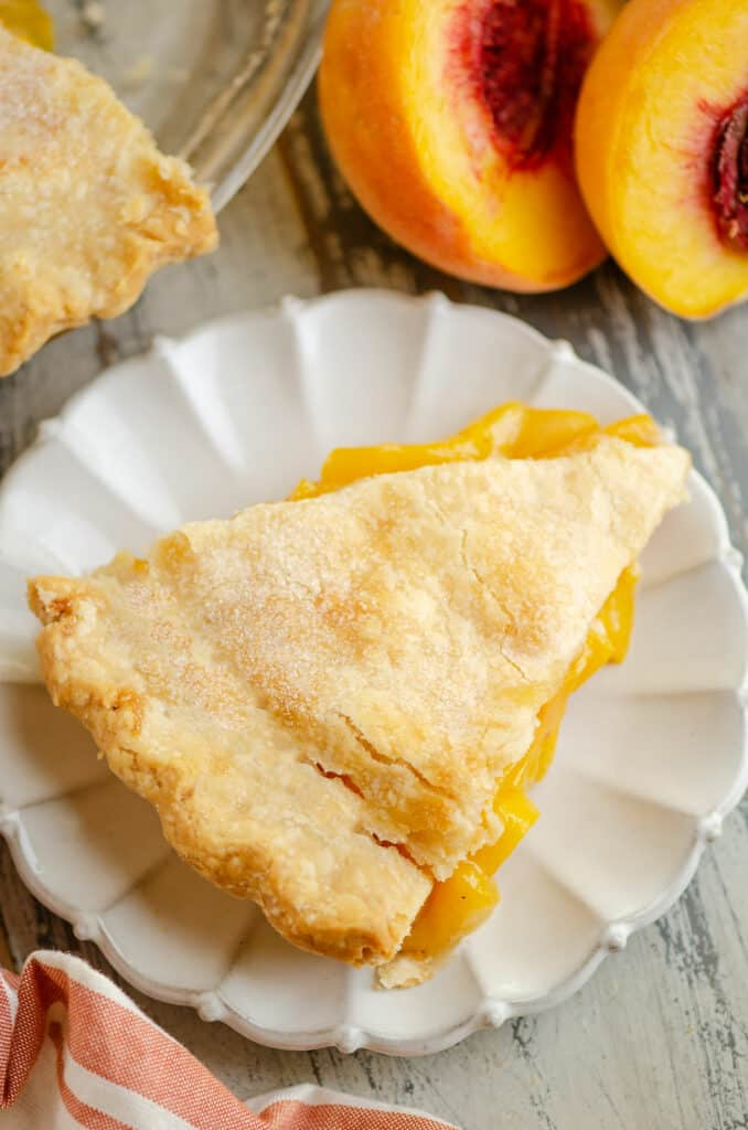slice of peach pie served on scalloped plate