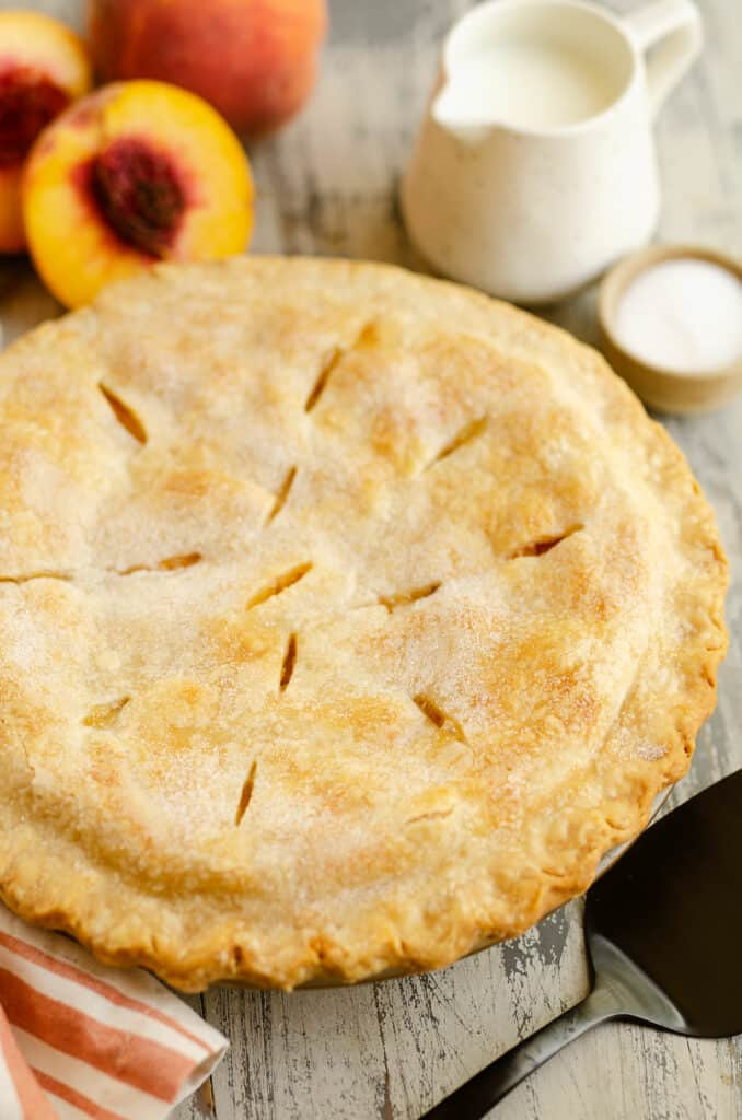 peach pie with flakey crust in pan