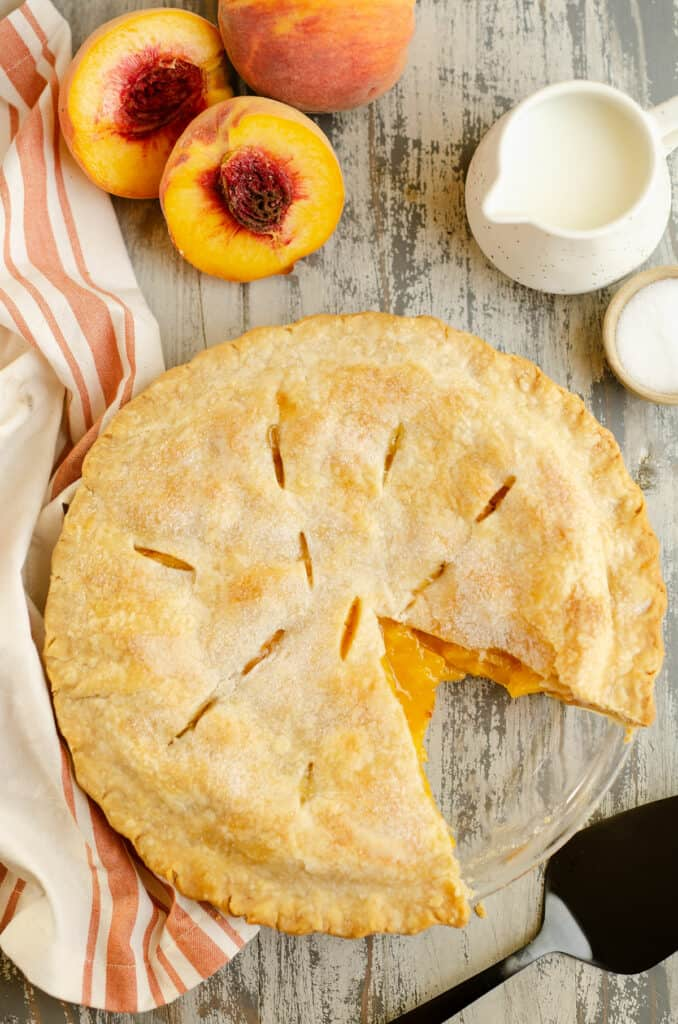 peach pie in pan with slice removed